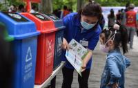 5月23日,垃圾分类指导员向孩子介绍指导手册上的垃圾分类小知_076531.jpg